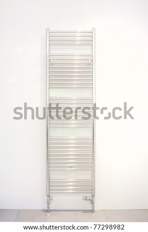 heated towel radiator hung on a bathroom wall