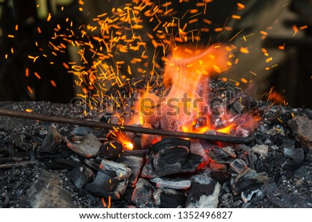 Heating a metal rod in a vintage forge fire or forging furnace. Fire, flame and sparks