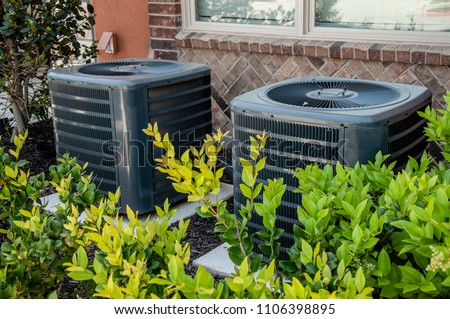 Heating and air conditioning units on the side of a brick building