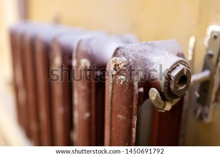 Heating cast-iron radiator  in apartment that is under construction, remodeling, renovation, overhaul, extension, restoration and reconstruction. Concept of home improvement.