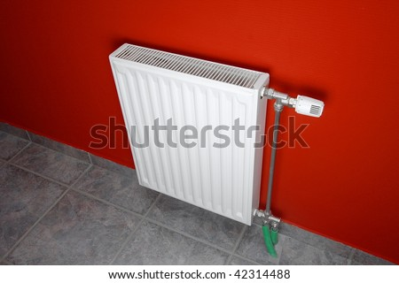 Heating radiator in a room with red wall