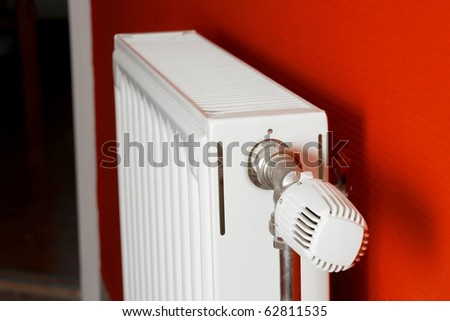 Heating radiator in a room with red wall, shallow focus