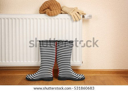 Shutterstock Heating radiator with rubber boots and warm clothes indoor