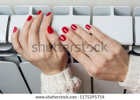 Heating white radiator in the apartment, female hand on the radiator.
