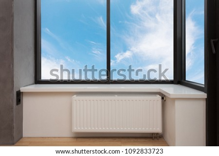Heating white radiator with adjuster of warming in living room under a large window.