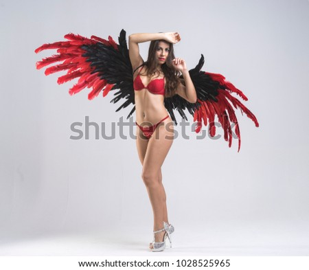 Stock Photo Heaven, angel woman, young woman dressed in red underwear with big wings of black feathers and garnets on neutral background