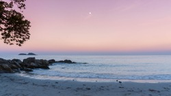 Heavenly peaceful beach in pastel color morning light good for mentally health. The sand beach and calm sea in pastel sunrise morning with a bright star in the sky. No people during pandemic covid19.