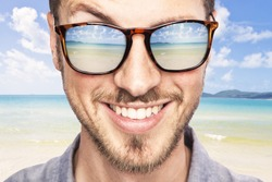 heavenly tropical destination reflected in young beautiful man's sunglasses. joyful portrait