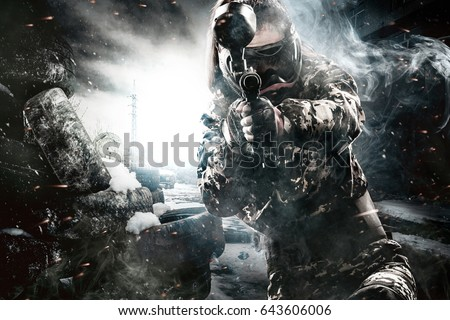 Heavily armed masked paintball soldier on post apocalyptic background. Ad concept. #643606006