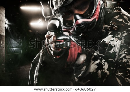 Heavily armed masked paintball soldier on post apocalyptic background. Ad concept. #643606027