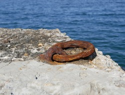 heavily rusted iron mooring ring with the harbor in the background. An old rusty metal mooring ring on the mooring wall on a sunny summer day. A device for holding sea vessels in port.