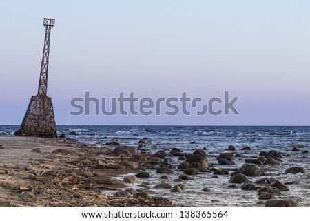 Heavily tilted old lighthouse on the shore