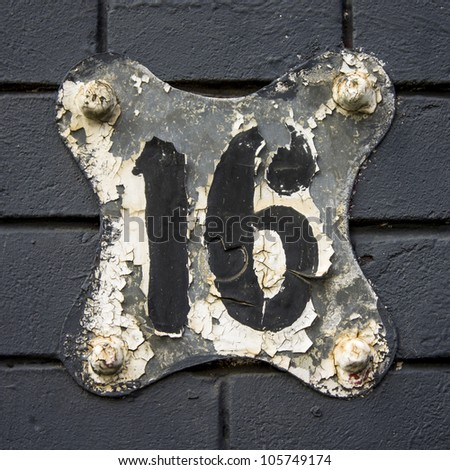 heavily weathered house number sixteen on a free form shaped plate