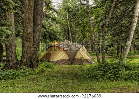 Heavily wooded camp site with a large tent set up for the night