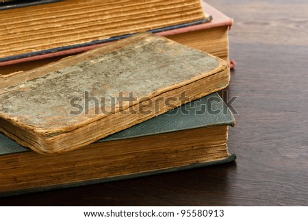 Heavily worn antique books piled on a wood table
