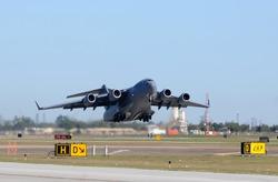 Heavy air force cargo jet taking off in haze