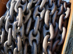 Heavy anchor iron metal chains in a pile by the port