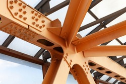 Heavy Beams And Chanals Of Steel Bridge Construction Painted Orange Paint. Metal Framework Of Structure Closeup.