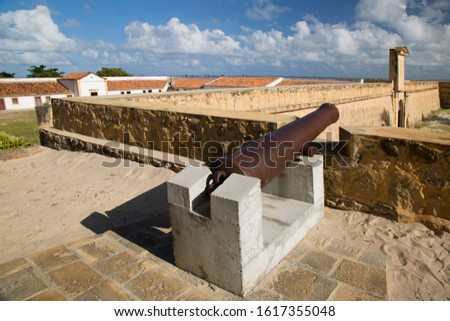 heavy bronze cannon in Dutch historical 17th century fort near the shoreline on the beach
