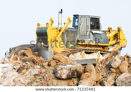 Heavy bulldozer loader at winter frozen soil moving and excavation works in sandpit - stock photo