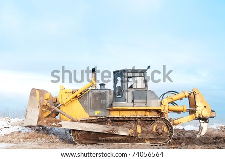 Heavy bulldozer loader at winter frozen soil ripping, moving and excavation works in sandpit
