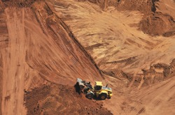 Heavy bulldozer loading red sand, an aerial view