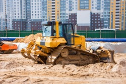 Heavy bulldozer on the construction of sewage and heating communications under the road, amid multi-story residential buildings