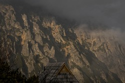 Heavy clouds rising over the crags on the slope of High Tatra Mountains, Poland. Spooky atmosphere caused by dark evening. Selective focus on the rocks, blurred background.