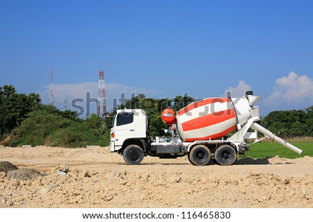 Heavy concrete truck on construction site against blue sky