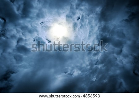heavy dramatic clouds,  with sun beaming through