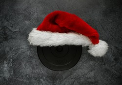 Heavy dumbbell weight plate with red Santa Claus hat for Christmas. Healthy fitness lifestyle holiday season concept, flat lay.