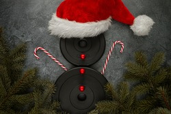 Heavy dumbbells weight plates, shaped as a snowman with red Santa Claus hat, candy canes as hands and decorative baubles as buttons. Healthy fitness lifestyle Christmas concept with tree branches.