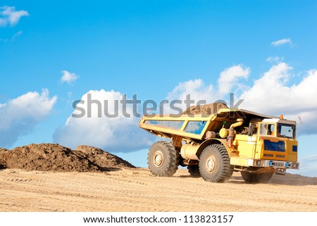 Heavy Dump Truck unloads soil on the sand at Construction Site