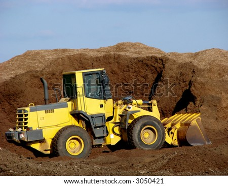 Heavy duty articulated excavator working in a pile of fresh dirt on a construction site