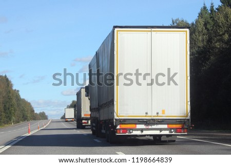 Heavy duty busuness transportation in export-import logistics - three white semi-trailer trucks rides on asphalt highway in summer against green trees, road signs and blue sky, rear-side view #1198664839