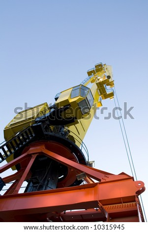 Heavy duty crane in yellow and orange. It has a copy space on top.