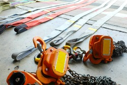 Heavy duty industrial fabric sling wire slings set with color coding and chains lifting hook equipment on the ground.
