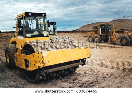 heavy duty machinery working on highway construction site. Bulldozer, dumper truck, soil compactor and vibratory roller