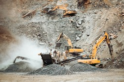 Heavy duty machinery working on quarry. Open pit ore mine details with excavator and bulldozer and hydraulic crusher