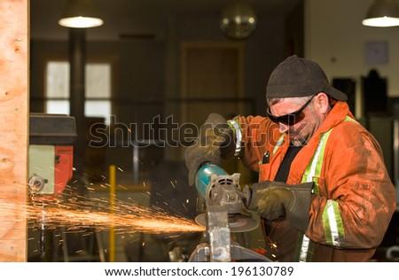 Heavy Duty Mechanic Wearing Orange Overalls, Grinding A Piece Of ...