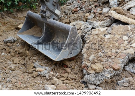 Heavy duty metal digger bucket among piles of rough earth and concrete rubble, excavating a driveway