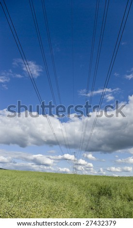 Heavy duty power cables running towards a pylon in the far distance set against a bright blue cloudy sky