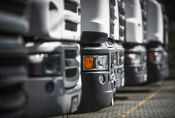 Heavy Duty Transportation industry. Line of New and Pre-Owned Semi Trucks on Dealership Sales Lot.