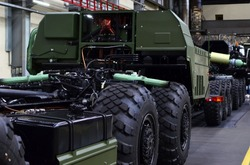 Heavy duty truck for transport missile defence system and non-standard cargo. Industrial workshop for the production of military trucks, wheel chassis and vehicles. Wheeled tractor background