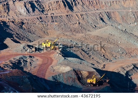 Heavy equipment digs and hauls ore inside an enormus open pit mine of Kursk Magnetic Anomaly