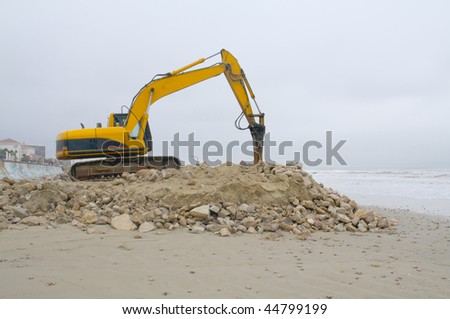Heavy equipment moving sand and rocks on the beach - stock photo
