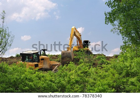Heavy equipment strips all the vegetation off the side of a hill - stock photo