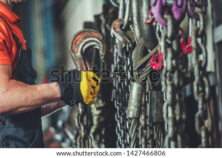 Heavy Equipment Support Chains and Hooks. Worker Looking For the Right Hauling Chain.