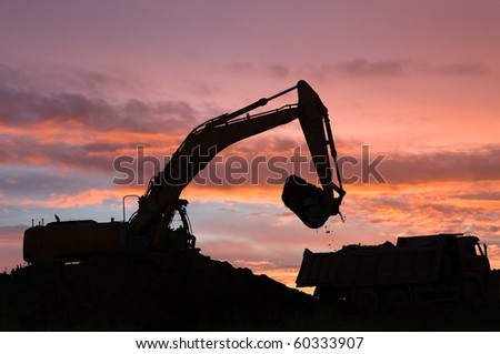 Heavy excavator loading dumper truck with sand in sandpit at dawn