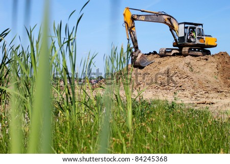Heavy excavator on stack of earth